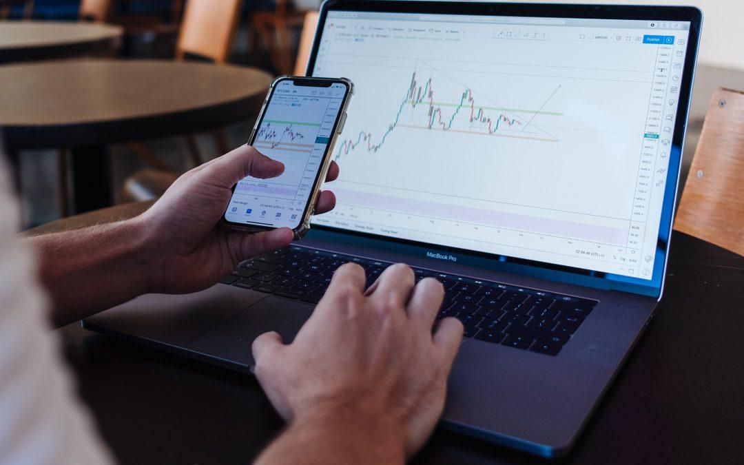 Mann mit Handy und Laptop auf dem Aktienkurse zu sehen sind